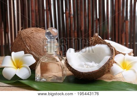 Composition with coconut oil in bottle for spa treatment on palm leaf