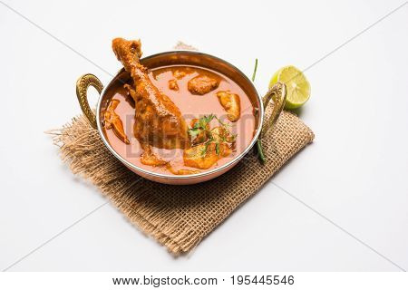 Indian spicy Chicken curry or masala chicken with prominent leg piece, popular recipe from India, selective focus