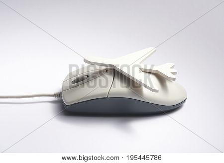 Online travel booking concept. Airplane shape on computer mouse