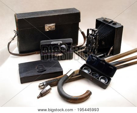 Old plate camera with historical photographic equipment on light cloth, still life includes convertible walking stick with tripod, set of filters in leather case and other objects