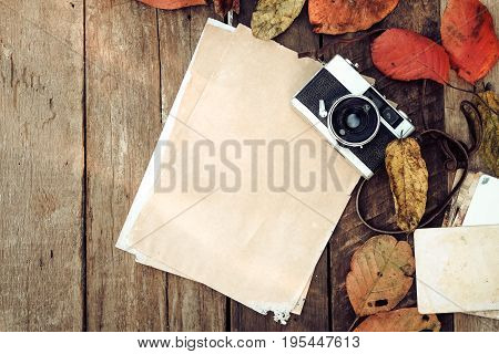 Retro camera and empty old instant paper photo album on wood table with maple leaves in autumn border design - concept of remembrance and nostalgia in fall season. vintage rustic style.
