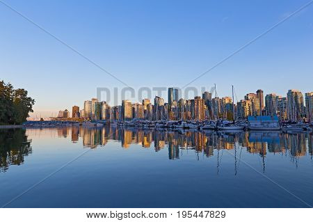 Vancouver downtown skyline reflection at sunset Canada. Scenic urban landscape as seen from Stanley Park.
