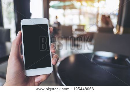 Mockup image of hand holding and raising white mobile phone with blank black screen in cafe