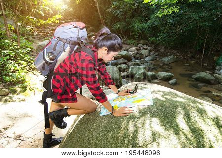 Women hiker with backpack checks map to find directions in wilderness area at waterfalls and forest. Travel Concetp.