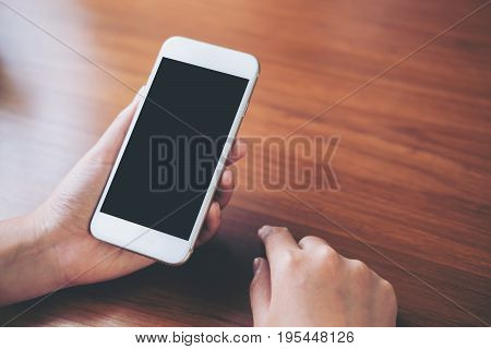Mockup image of hand holding white mobile phone with blank black screen on vintage wooden table
