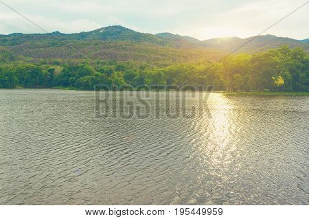 vintage tone image of lake and the mountain with beautiful blue sky in evening time at ang kaew in Chiang Mai University Thailand.