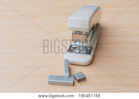 Stapler and staples on a wood background.