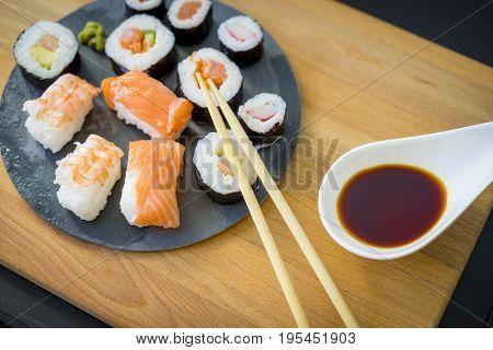 Nori on a wooden table on black slate plate with soy sauce and chopsticks