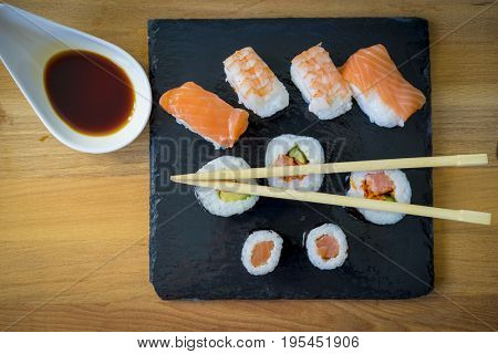 Sushi on a wooden table on black slate plate with soy sauce and chopsticks