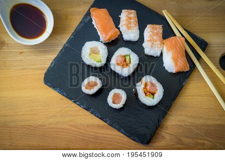Asian dinner, Sushi on a wooden table on black slate plate with soy sauce and chopsticks