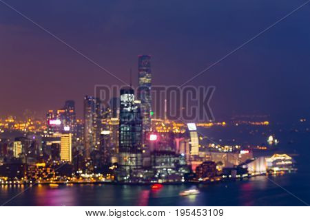 Night aerial view blurred bokeh light Hong Kong city over the bay abstract backgorund