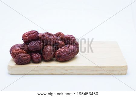 Dry red Jujube fruit on wooden board on white background