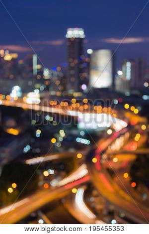Night blurred aerial view highway and city central business downtown with blue twilight sky abstract background