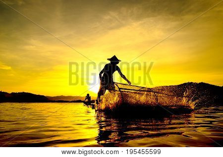 People fishing in river On the bright sky a beautiful golden color in Thailand.