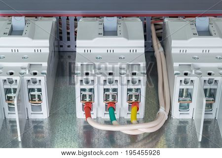 On the mounting panel there are three power circuit breaker. To one circuit breaker connected wires with ferrules. Tips of red green and yellow.