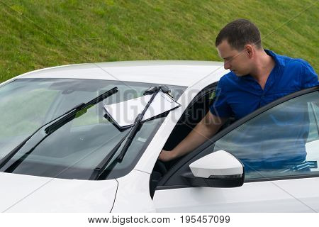 man in a blue shirt takes a white car for hire on vacation