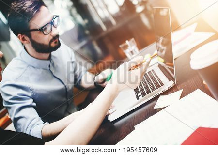 Young Bearded Businessman In Glasses Analyzes The Teamwork Done. Works At The Desk With A Laptop And