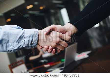 Two Managers In Casual Clothing In Meeting Room Handshakes After Finding Compromise