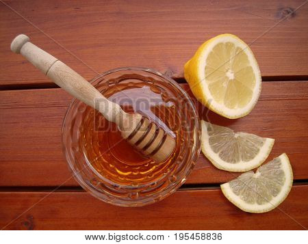 Honey in a glass bowl with honey dipper and lemon sliced on a wooden table.