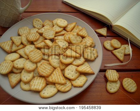 Crackers in a plate, cup of tea and open notebook on a wooden table.