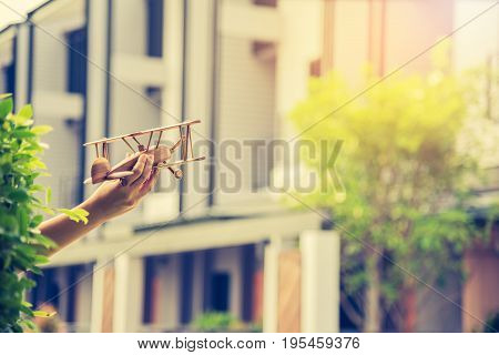 Hand Holding Wood Plane With Blur Townhome