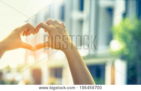 vintage tone image of hand touch together to make heart symbol with blur villa in background.