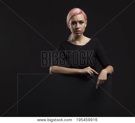 Young sexy woman portrait of a confident businesswoman showing presentation, pointing placard background. Ideal for banners, registration forms, presentation, landings, presenting concept.
