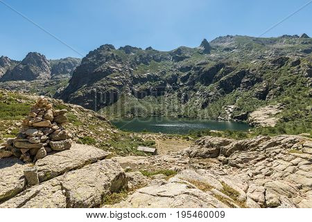 Stone Cairn Overlooking Lac De Melo In Mountains Of Corsica
