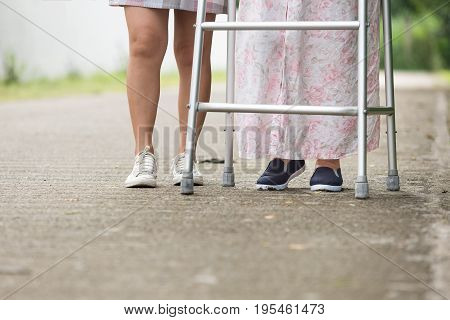 senior woman using a walker with caregiver on street .