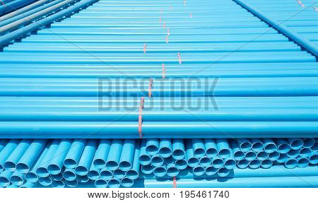 Blue PVC pipes stacked in warehouse .
