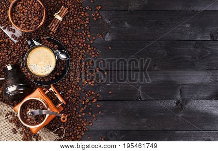 Coffee background, top view with copy space. Black cup of coffee, ground coffee, mill, bowl of roasted coffee beans on dark wooden background