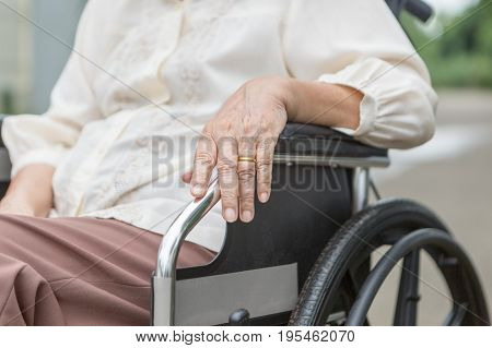 Elderly hands on a wheelchair at home .