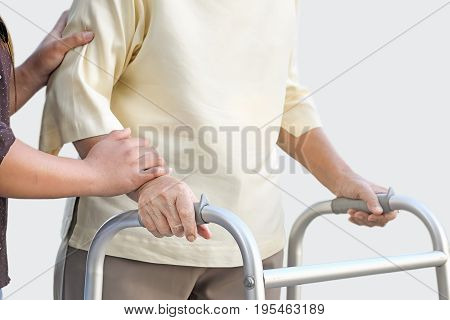senior woman using a walker with caregiver .