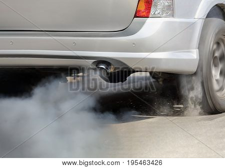 Air pollution from vehicle exhaust pipe on road .