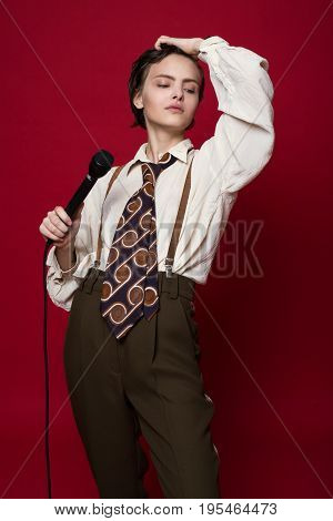 Fashionable Beautiful Singer Girl In Retro Coat, Tie And Pants With Microphone In Hands Posing On Re