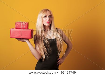 Attractive Young Blondy Woman Holding Red Gift Boxes Over Yellow Background.