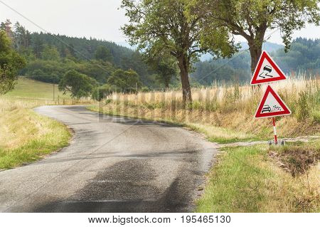 Road warning sign on slippery road. Spilled gravel on the road. Country road in the Czech Republic