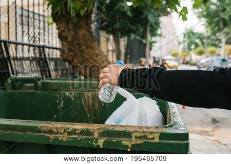 A man in the street throws a plastic bottle into a container with waste. Care for the environment. Eco friendly.