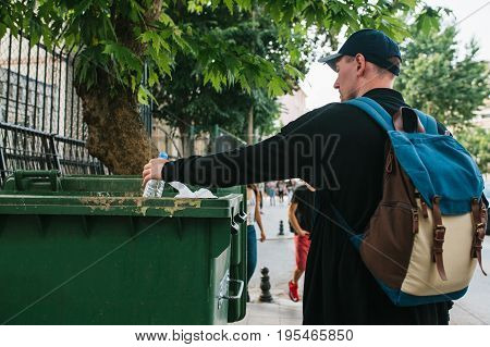 A tourist with a backpack and in a baseball cap on the street throws a plastic bottle into a container with waste. Care for the environment. Eco friendly.