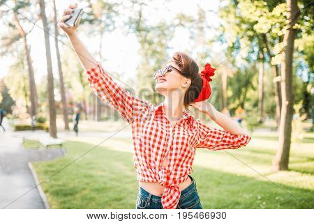Pinup sexy lady makes selfie on camera in park