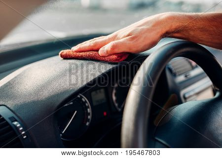 Male hands cleans auto, car dashboard polishing