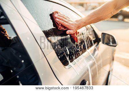 Male hand rubbing car window with foam, carwash