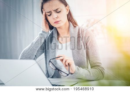 Young woman is tired and feels stressed out. Frustrated she closed eyes and massage temples head.