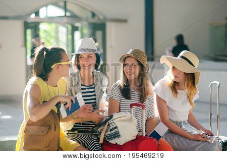 Young tourists waiting for the flight. Girlfriends discuss something. Each girl in a hand has a passport and tickets. Nearby baggage. Summer holiday. Interesting travel.