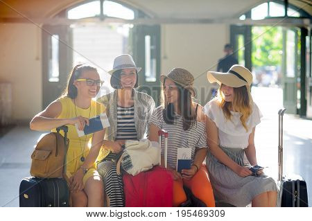 Cheerful girls at the station. Young tourists in an anticipation of cheerful rest. Girlfriends briskly talk. In hands at girls of the passport and tickets. Summer vacation.