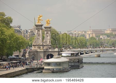 ParisFrance- April 29 2017: View of the Alexander lll Bridge . By the embankments are moving pedestrians