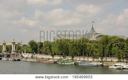 ParisFrance- April 29 2017: View of the embankment of Por de Sham Elise and the Grand Palace. On the waterfront are pedestrians