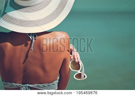 Sexy Back Of A Beautiful Woman In Striped Bikini And Hat With Creative White Sunglasses On Sea Backg