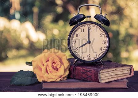 An old alarm clock a stack of books and a rose on a wooden table. Books a watch and a rose on a green natural background. Vintage tinting