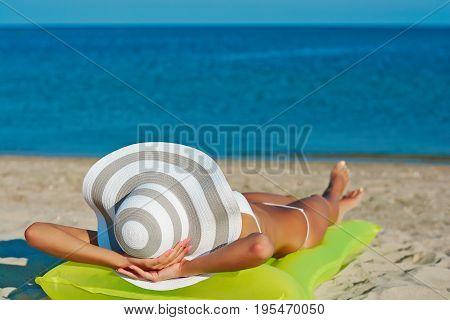 Beautiful Happy Woman In White Bikini With Yellow Inflatable Mattress On The Beach